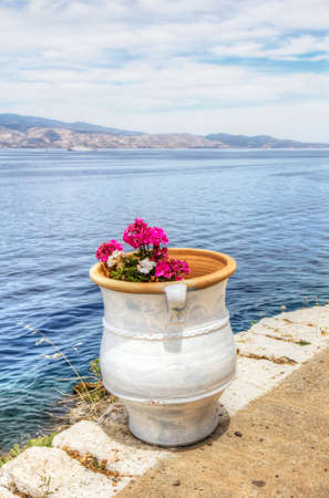 aegean sea: Colourful pink and white flowers in white clay pot overlooking the Saronic Gulf in Hydra island in the Aegean Sea, Greece. Stock Photo