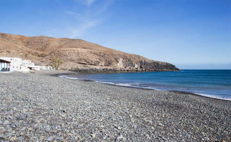 Beach with pebbles in the small fishing village of Giniginamar on the south east coast of Fuerteventura, Canary Islands, Spain. Stock Photo