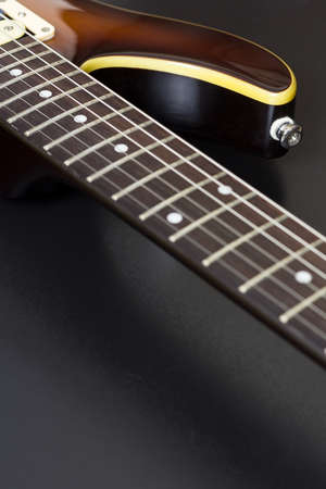 Closeup of a sunburst electric guitar with shallow depth of field on black and with copy space
