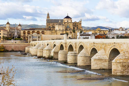 Ancient Roman Bridge across the river Guadalquivir in Cordoba. Cordoba Mosque and Cathedral is in the background. This bridge was featured in TV series Game of Thrones as the Long Bridge of Volantis.