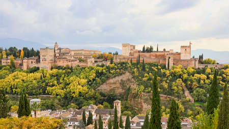 Panoramic scenic view of the Alhambra of Granada from the Albaicin with cloudy sky, Andalucia, Spain.