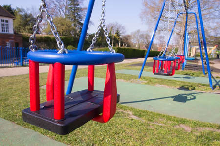 Empty swings in children's playground in England during lockdown due to coronavirus quarantine for the prevention of COVID-19.
