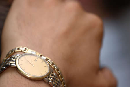 mans watch: gold watch on the mans hand Stock Photo