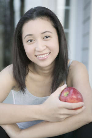 way of behaving: Portrait of a young woman sitting holding an apple LANG_EVOIMAGES