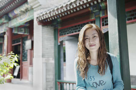 voguish: Young woman standing outdoors looking at camera smiling, Beijing, China LANG_EVOIMAGES