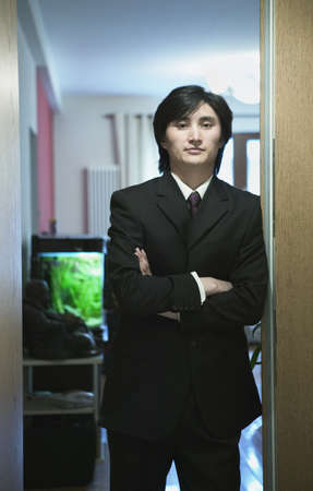 effrontery: Businessman standing in a doorway, Beijing, China LANG_EVOIMAGES