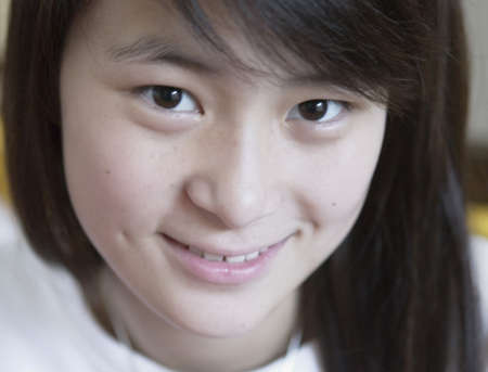 effrontery: Close-up of a teenage girl looking at camera smiling, Beijing , China LANG_EVOIMAGES