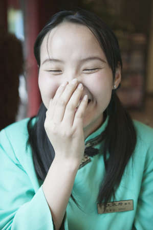 invariable: Waitress laughing with a hand over her mouth, Beijing , China LANG_EVOIMAGES