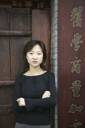 effrontery: Young woman standing against a door with arms folded looking at camera, Beijing, China