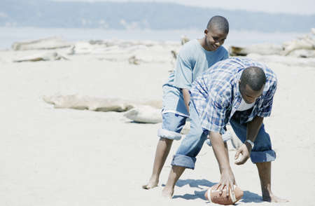 Father playing football with his son on the beach LANG_EVOIMAGES