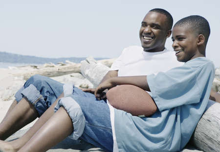 Father sitting with his son on the beach LANG_EVOIMAGES
