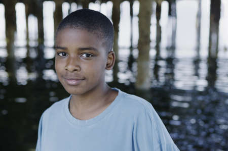 Portrait of a young boy smirking looking at camera under a pier Stock Photo - 16043363