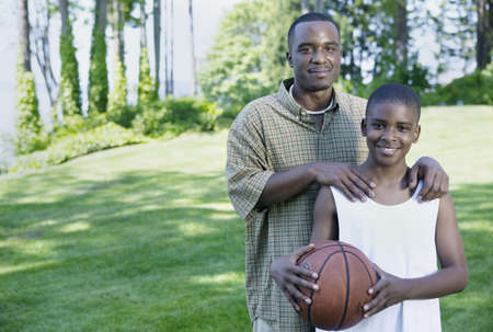 member of the clergy: Father and his son smiling holding a basketball LANG_EVOIMAGES