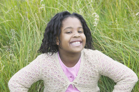 way of behaving: Young girl sitting on grass smiling looking at camera