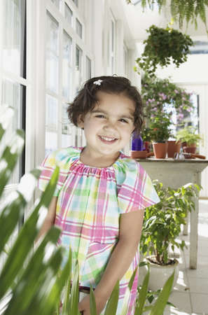 way of behaving: Young girl standing near a door smiling in a greenhouse LANG_EVOIMAGES