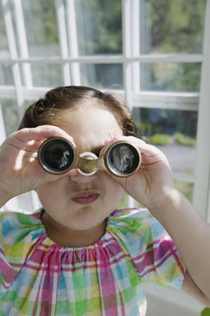 blase: Young girl looking through binoculars in a greenhouse