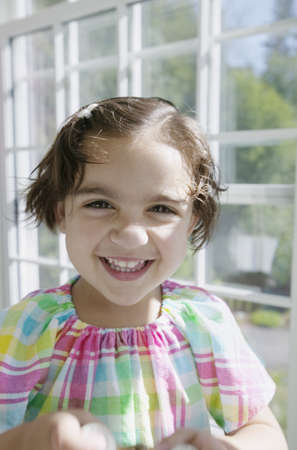 ebullient: Young girl looking at camera smiling in a greenhouse LANG_EVOIMAGES