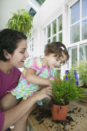 largesse: Mother and her daughter gardening in a greenhouse LANG_EVOIMAGES