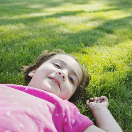 exuberant: Young girl lying on the grass smiling LANG_EVOIMAGES
