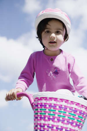 Low angle view of a young girl riding a bicycle wearing a helmet Stock Photo - 16043372