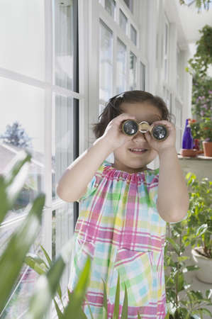 way of behaving: Young girl looking through binoculars in a greenhouse