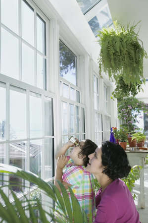 Mother and daughter looking out window of greenhouse LANG_EVOIMAGES