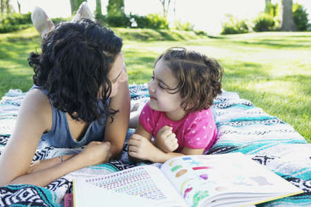 largesse: Young girl and her mother lying on a lawn looking at each other LANG_EVOIMAGES