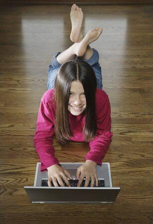 Teenage girl lying on the floor working on a laptop Stock Photo - 16043376