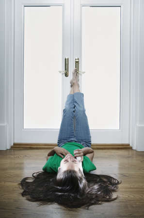 tlingit: Teenage girl lying on the floor talking on a phone with her legs up against a door LANG_EVOIMAGES
