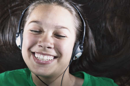 Portrait of a teenage girl wearing headphones smiling Stock Photo - 16043380