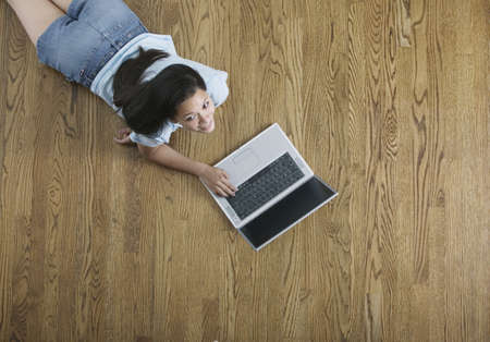way of behaving: High angle view of a teenage girl lying on the floor working on a laptop