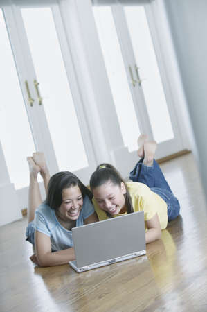 restfulness: Two teenage girls lying on the floor working on a laptop