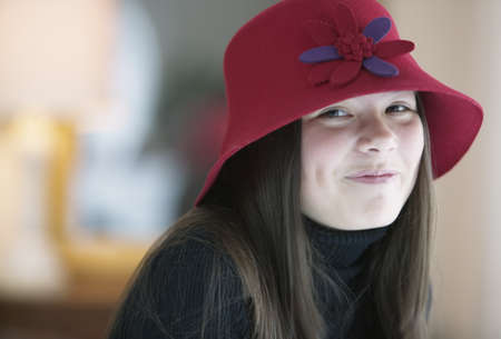 impersonal: Teenage girl wearing a hat looking at camera smirking LANG_EVOIMAGES