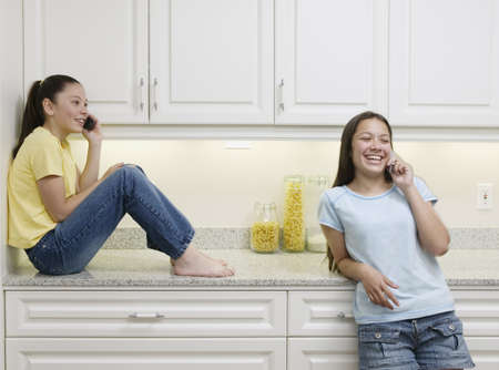 tlingit: Two teenage girls in a kitchen talking on mobile phones