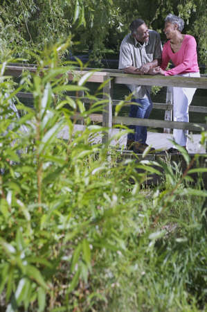 Elderly couple standing together leaning on a wooden railing in a park LANG_EVOIMAGES