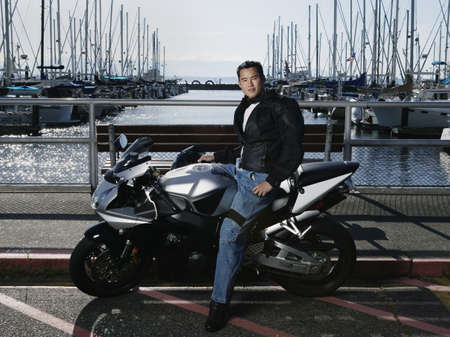 courier: Portrait of a young man sitting on a motorcycle at a dock