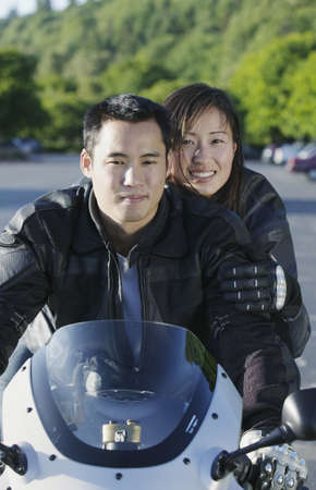 Portrait of a young couple sitting on a motorcycle Stock Photo - 16043397