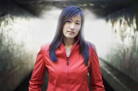 way of behaving: Portrait of a young woman looking at camera in front of tunnel