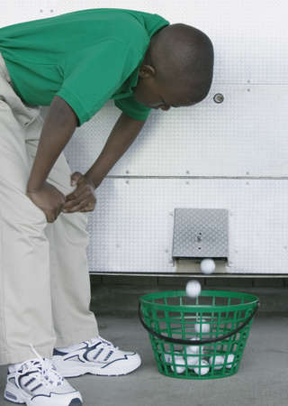 Young boy bending forward looking at a golf ball vending machine at a golf course LANG_EVOIMAGES