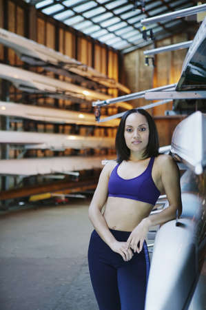 way of behaving: Young woman in crew boathouse leaning against (boat) shell
