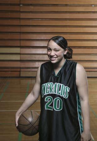 way of behaving: Teenage girl basketball player holding a basketball laughing on a basketball court LANG_EVOIMAGES