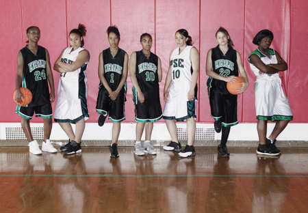 reflect: Team of female teenage basketball players lined up against wall LANG_EVOIMAGES