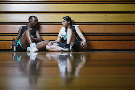 Two teenage girl basketball players sitting on the floor resting against bleachers