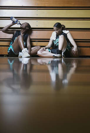 african solidarity: Two teenage girl basketball players sitting on the floor resting against bleachers
