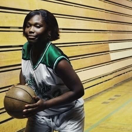 Teenage girl basketball player holding a basketball on a\ basketball court