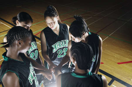 confab: Team of female teenage basketball players in a huddle on a basketball court