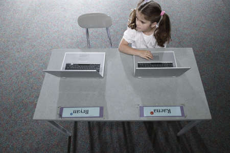 pedagogic: High angle view of a young girl sitting in a classroom at school working on a laptop