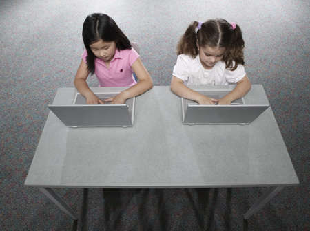 High angle view of two young girls sitting in a classroom at school working on laptops Stock Photo - 16043440