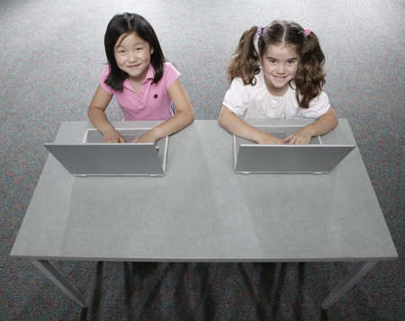 High angle view of two young girls sitting in a classroom at school working on laptops LANG_EVOIMAGES