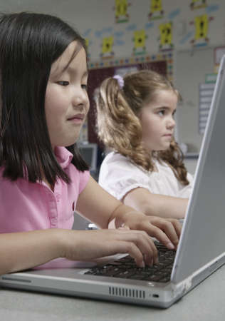 pedagogic: Two young girls sitting in a classroom at school working on laptops